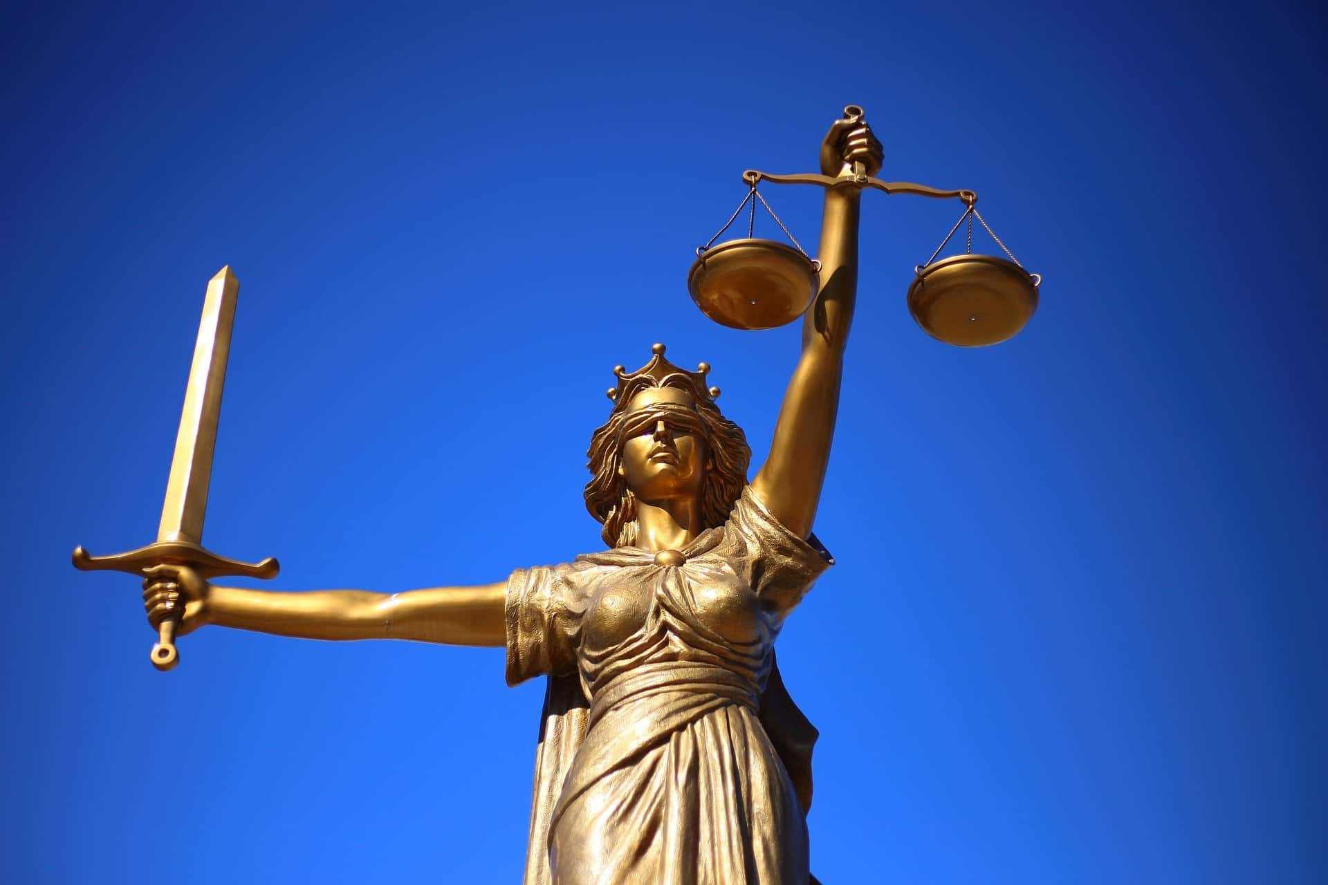 the lady of justice holding sword and scales against a blue sky